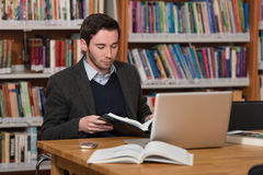 Young Student Using His Laptop In A Library. In The Library - Handsome Male Student With Laptop And Books Working In A High School - University Library - Shallow Stock Photography