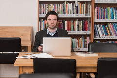 Young Student Using His Laptop In A Library Stock Images