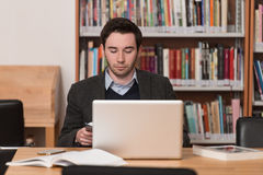 Young Student Using His Laptop In A Library. In The Library - Handsome Male Student With Laptop And Books Working In A High School - University Library - Shallow Stock Photo