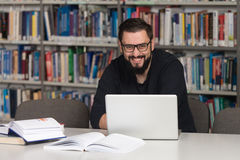 Young Student Using His Laptop In A Library Royalty Free Stock Photography