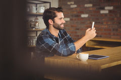 Young student using his smartphone. In cafe Royalty Free Stock Images