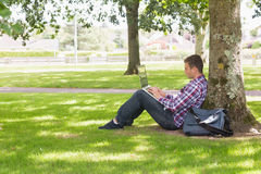 Young student using laptop outside. On college campus Royalty Free Stock Photos