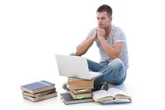 Young student using laptop studying. Young college student using laptop, sitting among books, using headset Royalty Free Stock Photos