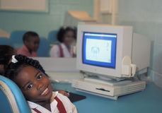 Young student with vintage Apple computer. PORT-OF-SPAIN, TRINIDAD AND TOBAGO - MAY 3, 1995. Young girl in tthe computer room in a school of Port of Spain Royalty Free Stock Photography