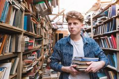 Free Young Student Walking In A Library With Books In His Hands And Looking For Literature Stock Image - 140976301