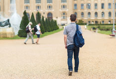 Young student walking to the university. Back view. Photo Stock Photos
