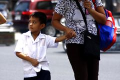 A young student walks with his mother going to school. Stock Images