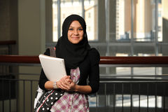 Young Student wearing a veil. And holding a copybook with college building on background Stock Photos