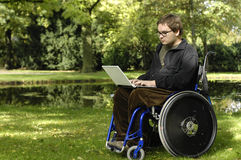Young student on a wheelchair at the park. Student on a wheelchair learning at the park Royalty Free Stock Images