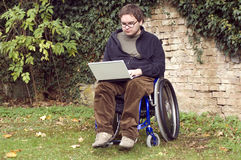 Young student on a wheelchair at the park. Student on a wheelchair learning at the park Stock Images