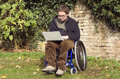 Young student on a wheelchair at the park. Student on a wheelchair learning at the park Royalty Free Stock Image