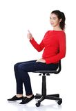 Young student woman on armchair showing thumbs up Stock Image
