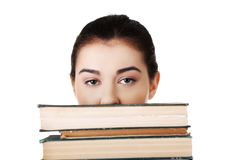 Young student woman hiding behind books Royalty Free Stock Images