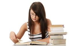 Young student woman with lots of books studing. Royalty Free Stock Images