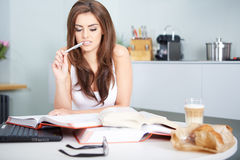 Young student woman with lots of books studying Royalty Free Stock Image