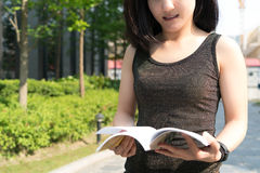 A young student woman is reading a book on hand Stock Image
