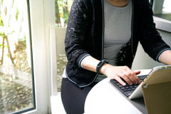 Young student women wearing smart band using tablet computer Stock Images