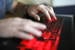 Young student working on laptop. Fingers are on the keyboard Stock Photography