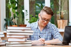 Young student working in a library. Portrait of a handsome smart student wearing glasses and blue checkered shirt sitting at the table in a library and making Stock Photography