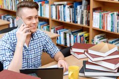 Young student working in a library. Portrait of a handsome smart student wearing glasses and blue checkered shirt sitting at the table in library talking on a Royalty Free Stock Image