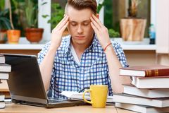 Young student working in a library. Portrait of a handsome smart student wearing glasses and blue checkered shirt sitting at the table in library thinking and Royalty Free Stock Photo