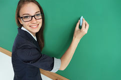 Young student writing on blackboard. Royalty Free Stock Images