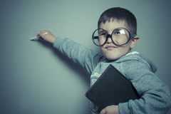 Young student writing on a blackboard school with a book in hand. And big glasses Royalty Free Stock Images