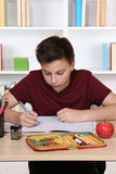 Young student writing in his exercise book at school Royalty Free Stock Images