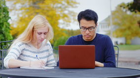 Young students - Asian man and Caucasian woman engaged outdoors. stock video footage