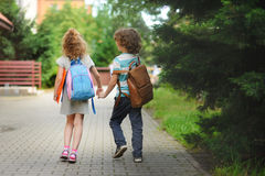 Young students, boy and girl, going to school. Stock Images