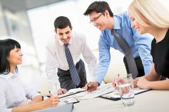 Young students. A business team of four plan work in office Stock Image
