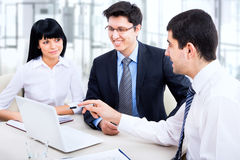 Young students. A business team of four plan work in office Royalty Free Stock Image