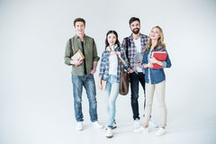 Young students in casual clothes holding books on white Stock Photo