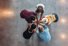 Young students celebrating success. Top view of group of young people putting their hands together. Young students standing in a circle making stack of hands Stock Photo