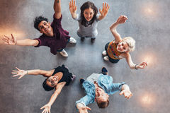Young students celebrating success. Top view of young students standing together looking up at camera with their hands raised in celebration Stock Photo