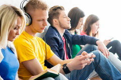 Young students chilling out after the lesson. Group of students on a break reading books and using smartphones. Focus on a teenage boy and girl. Background is Stock Photography