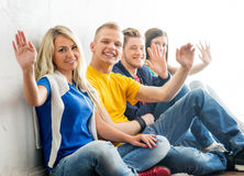 Young students chilling out after the lesson. Group of happy students on a break waving. Focus on a boy and a girl. Background is blurry Royalty Free Stock Photography