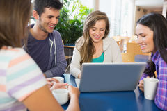 Young students doing assignment on laptop together Stock Images