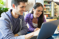 Young students doing assignment on laptop together Stock Photos