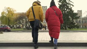 Young students goes to the university. Pretty girl and guy wearing warm clothes up stairs and walks forward. The people goes to the campus. Students talks stock video