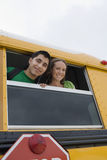 Young Students Listening Music. High school couple listening to music while looking through school bus window Royalty Free Stock Photos