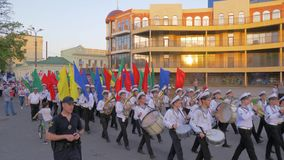 Young students Marine Academy march in a parade with musical instruments and colorful flags along the main street of the. Kherson, Ukraine - May 20, 2019 stock video