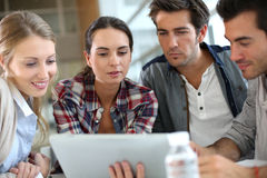 Young students meeting and using tablet Royalty Free Stock Image