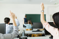 Young students raising hands in a classroom Royalty Free Stock Images