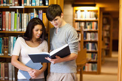 Young students reading a book. In a library Stock Photo