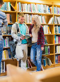 Young students reading book in the library. Portrait of two young students reading book against bookshelves in the library Stock Photo