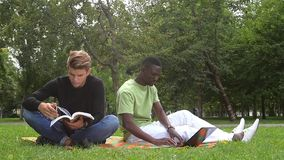 Young students reading books at the school park stock video footage