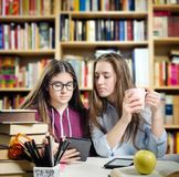 Young students reading an ebook. Over a desk full of various objects Royalty Free Stock Image