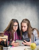 Young students reading an ebook. Over a desk full of various objects Stock Images