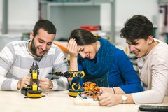 Young students of robotics preparing robot for testing. In workshop Stock Photo